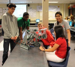 Jesus Torres, Marvin Beecher, Nicholas Nelson, Stephanie Montoya and Andrea Garcia inspect a robot during their eningeering class.