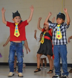 Pre-K students dance at the Summer Transition Program graduation.