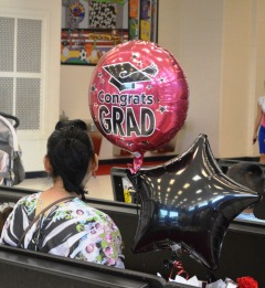A proud parent waits with a balloon for her recent Pre-K graduate.
