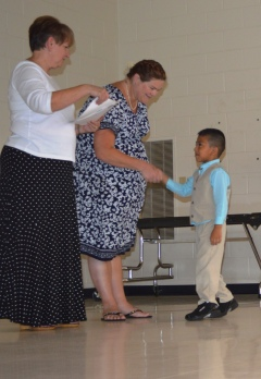 One Pre-K student shakes hands with his teacher as he receives his certificate from Blue Ridge Principal Lisa Goode.