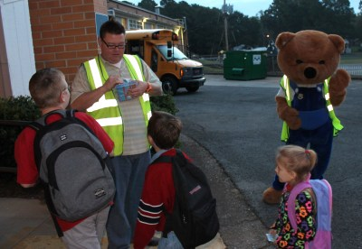Safety Bear greets Brookwood students as Robbie Moore gives out stickers during the evacuation drill.