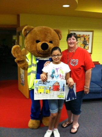 The Grand Prize winner in the District School Bus Safety Poster Contest was fourth grader Maria Rodriguez of Roan School. She is shown with Safety Bear and  DPS Director of Transportation BeLinda Parrish.