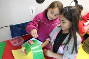 Ava Robbs and Rubi Medina see how many erasers they can place on a paper bridge before it falls.