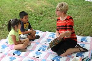 Annelle Scott reads to Karyme Juarez and Bran Ribas.
