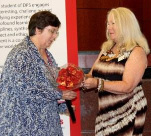 Jan Henderson was recognized at August's school board meeting for winning the LEA Award. Head Start's Teresa Millican hands Henderson flowers.