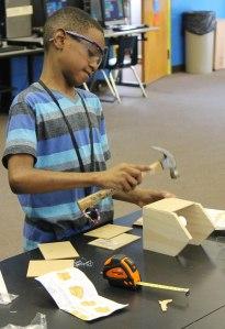 Keontae Farrar works on a birdhouse in the City Park STEM lab.