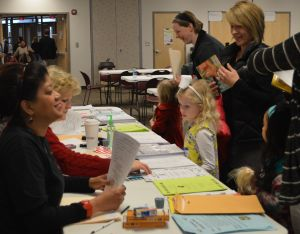 Lenise Waddell and Melody Shuford, at far left, register children for kindergarten in 2014.